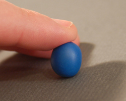 rolling a blue ball of clay