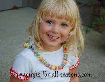 child wearing cereal necklace