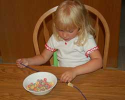 child making a cereal necklace