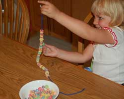 child making a fruit ring necklace