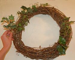 adding greenery to wreath