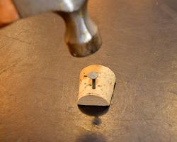 hammering nail in cork