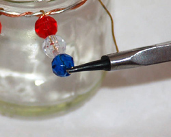 bending the end of the eye pin with jewelry pliers